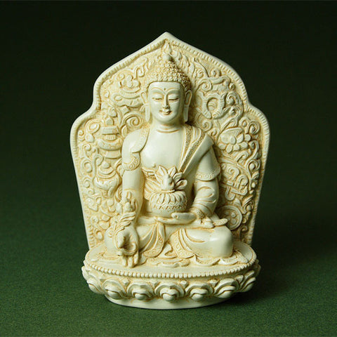Medicine Buddha sculpture, right hand in charity mudra, left hand holding bowl of healing herbs on his lap.