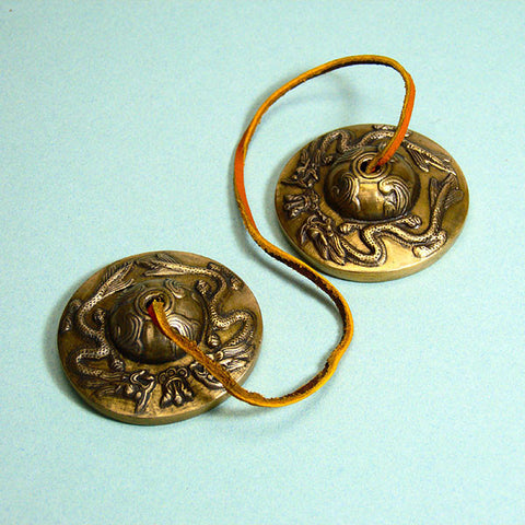 Tibetan Buddhist tingsha meditation bells, embossed with two dragons, guardians of spiritual and earthly wealth.