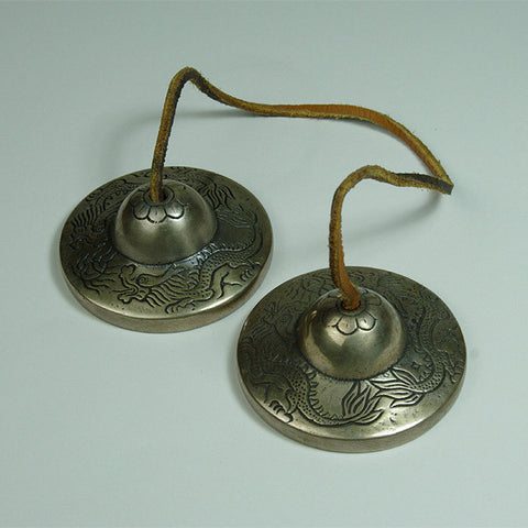 Tingsha meditation bells fom Tibetan Buddhist tradition decoratd with two engraved dragons.