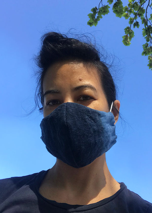 Seattle leather maker whips out fabric collected over her lifetime to make face masks.  In this photo she wears a mask made from vintage indigo dyed fabric that was hand woven in Japan. The deep indigo blue is offset by a light shade of indigo.