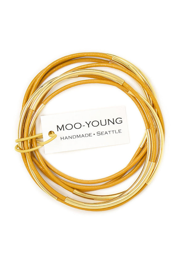 A stack of mustard colored leather bracelets with gold beads held together with a tag from Seattle maker Moo-Young.