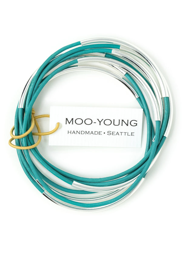 A stack of seven turquoise colored leather bracelets for women with silver beads.  The bracelets are displayed against a white background and looped together with the makers tag.