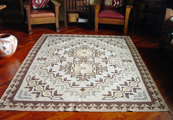 Design patterns often associated with the Two Grey Hills weavings include a border, four matching corner elements and a large central full or belted diamond.