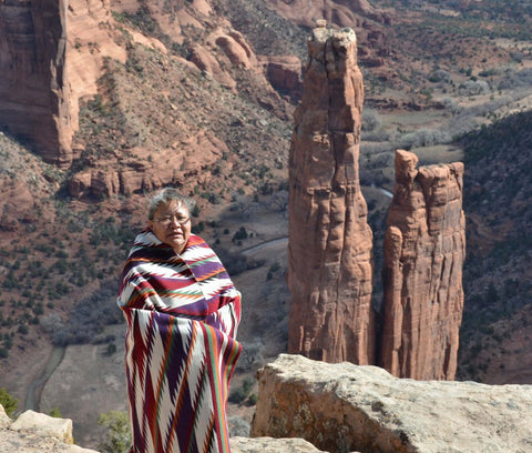 Cara Yassie wearing one of her weavings standing in front of Spider Rock