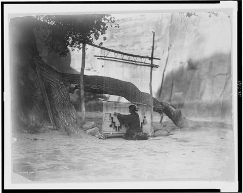 Navajo weaver at her outdoor loom in Canyon de Chelly. by E.S. Curtis, 1907