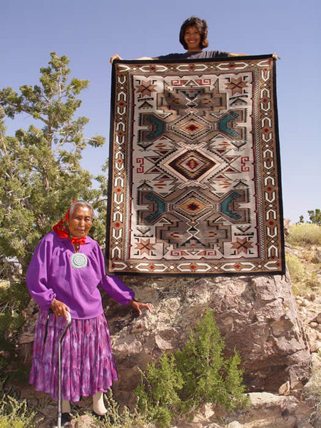 Grace stands next to her magnificent Teec Nos Pos weaving held by her daughter Helene