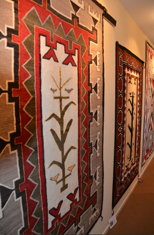 Tree of Life Native American Rug with Teec Nos Pos elements hanging at the Nizhoni Ranch Gallery