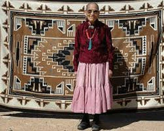 Master Weaver Clara Sherman standing in front of her Two Grey Hills weaving.