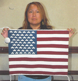 Navajo rug pictorial of the United States Flag held by weaver Jo Anne Begay