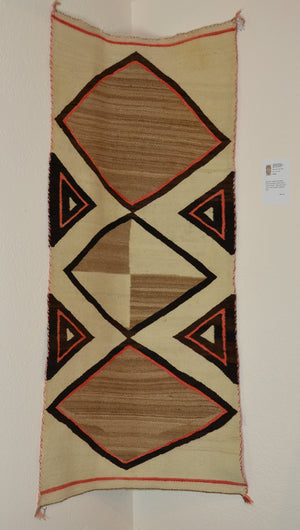 Vintage saddle blanket woven by a unknown Navajo weaver hung on the inside curve of the wall.