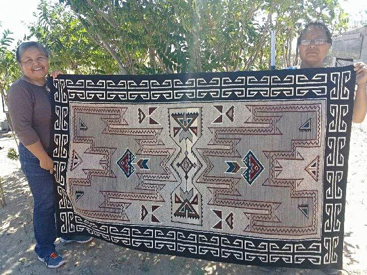 Cecelia Nez (L) with finished Navajo weaving