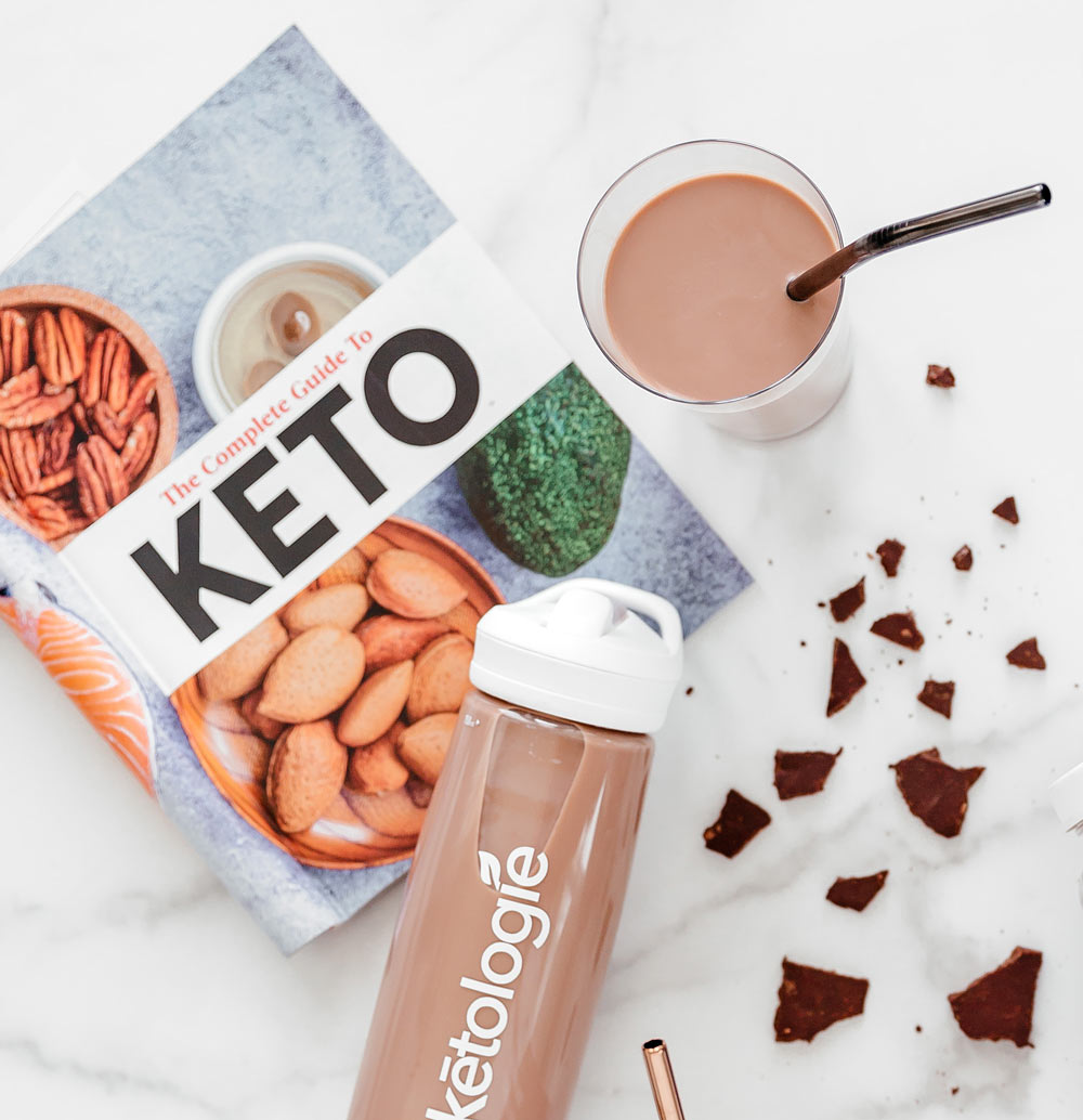 bottle of keto shake from ketologie lying in a table next to an already made shake and some cubes of dark chocolate