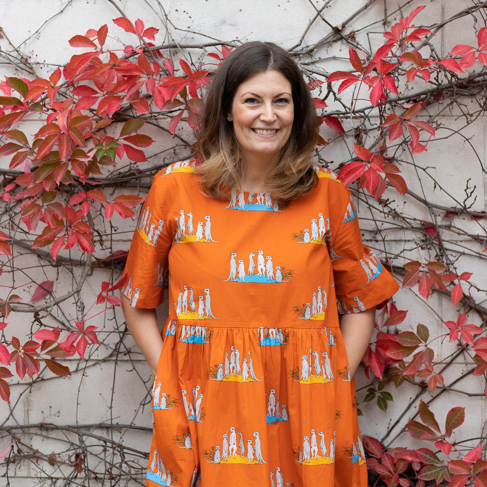 Woman wearing bright orange flame coloured dress with pockets and gathered drop waist dress is printed with groups of meerkat families.