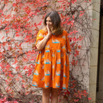 "Full length photo of a woman wearing an Oomph and Floss orange flame coloured dress featuring hand drawn illustrations of ""the bizzybuddies"" meerkat family.  The woman's hand is held to her face, she is standing against a wall that has a plant climbing across it with red autumn leaves."