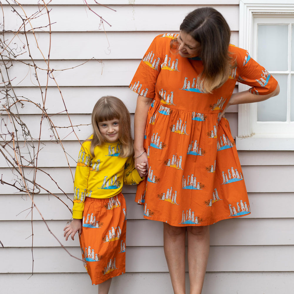 Matching Mum and Daughter bright colourful clothing.  Womens orange meerkat dress and girls orange meerkat skirt in matching material.  Girl wears matching yellow meerkat jumper from same print.