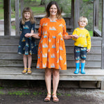 Mum and kids in matching scandi-like print clothing featuring bright colours and meerkat print.  Woman wears orange flame coloured meerkat dress.  Girl wears carbon dark grey girls twirling dress with meerkats.  Boy wears  Matching carbon grey shorts and yellow meerkat kids jumper.