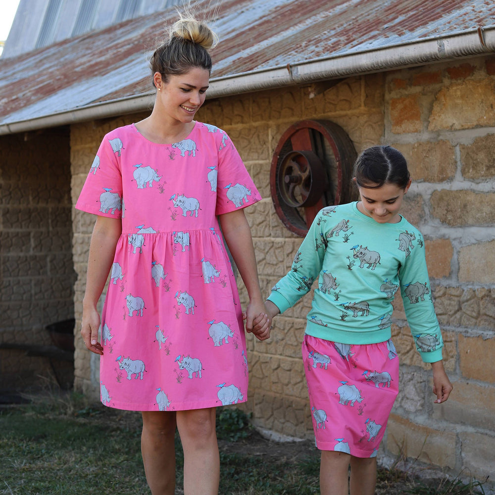 Woman wearing a knee length short sleeved cotton dress in bright pink featuring grey rhinos, she is holding hands with a young girl who is wearing a pink knee length skirt from the same fabric as the womens dress, the girl is wearing a biscay bay blue lightweight jumper featuring the same grey rhinoceros print in a repeat pattern.