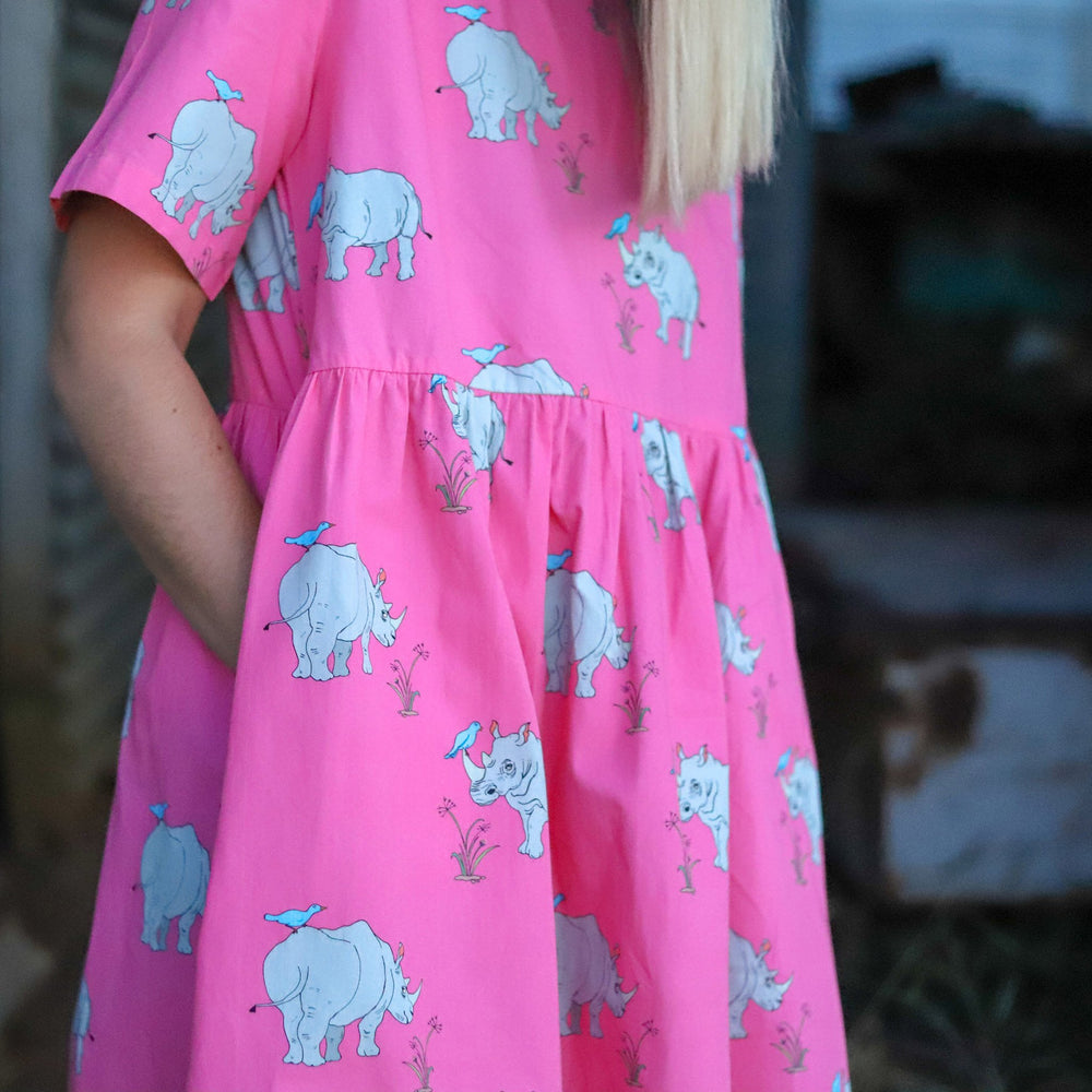 Close up of the a gathered drop waist and deep pockets of short sleeved womens dress in a vibrant pink lemonade colour featuring a repeat pattern of hand drawn illustrations of a grey Rhinoceros with a blue tick bird on its back