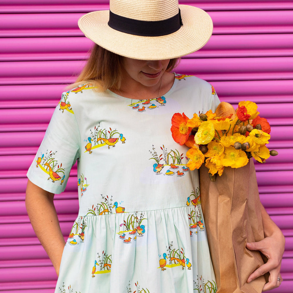 Woman wearing short-sleeved cool mint coloured dress with duck family print.  she is wearing a straw hat and carrying a bunch of yellow and orange flowers in a paper bag.  A bright pink garage door is in the background.
