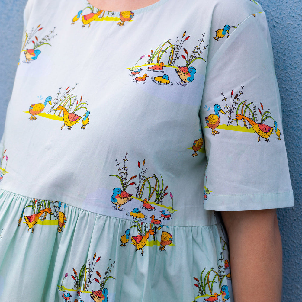 Close up of hand drawn duck illustration and gather waist line of short sleeved women's dress