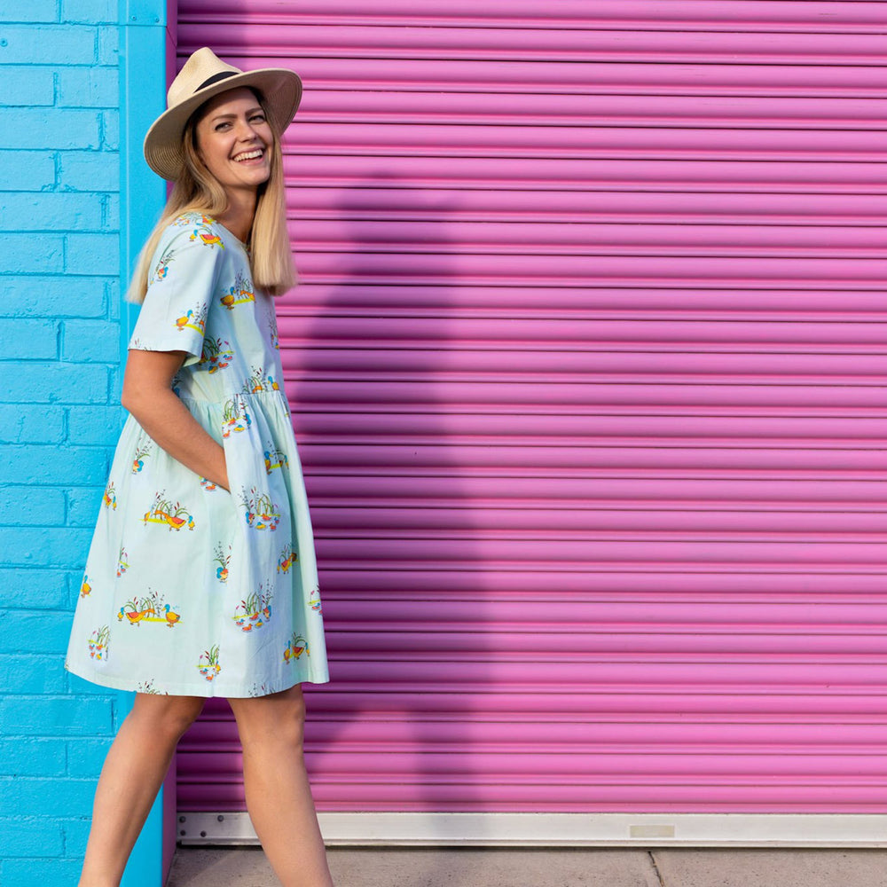 Women wearing dress in cool mint colour with Puckle Duck family print she has her hands in her pockets and is wearing a straw hat, she is walking past a bright blue brick wall and a bright pink roller garage door