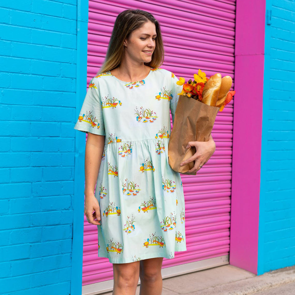 Woman holding bunch of flowers wearing a Mumma scandi style print dress with animal print of a duck family on a cool mint blue