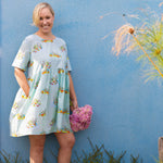 Woman wearing gathered waist Dress with pockets.  Dress features hand drawn illustration of ducks in a pond on a cool mint blue base fabric