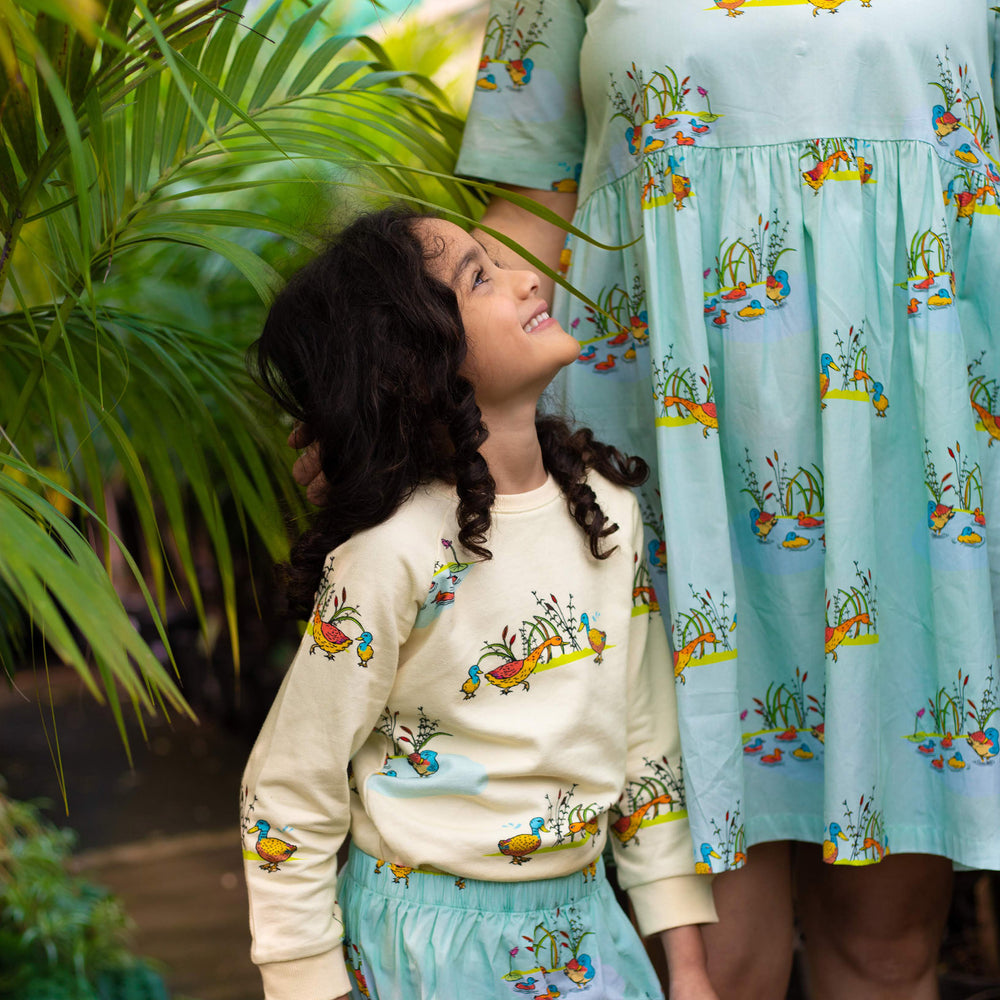 Mum and daughter wearing matching duck print clothing.  Girl wears cream duck jumper and mint duck skirt, Mum wears mint duck dress.