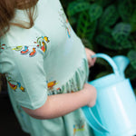 Close up of girls Aline dress showing gathered waistline.  Dress is a cool mint blue colour featuring hand-drawn duck illustrations in a repeat pattern.