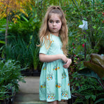 Girl standing in a plant nursery wearing a short sleeved Aline dress with a gathered waistline.  Dress is a cool mint blue colour featuring hand-drawn duck illustrations in a repeat pattern.