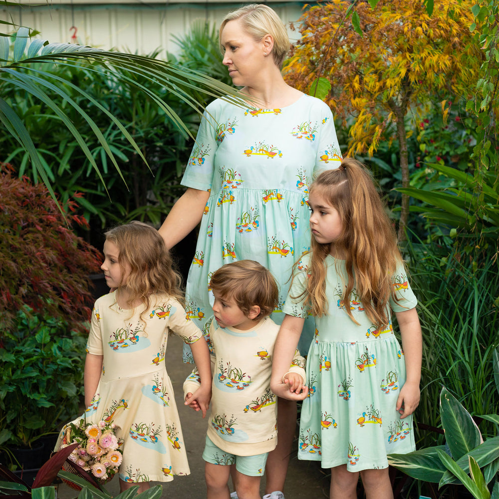 Mum and kids wearing matching scandi-like outfits.  Mum wears dress in cool mint blue with Puckle Duck family print.  Girl on the left wears cream twirling dress with duck print.  Boy wears short sleeved tee with duck family print and matching drawstring shorts in duck print.  Girl on right wears A line dress in mint with duck print.