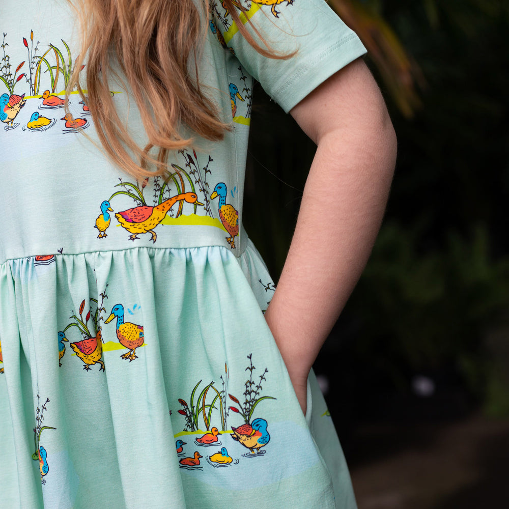 Close up of girls Aline dress showing gathered waistline and pocket.  Dress is a cool mint blue colour featuring hand-drawn duck illustrations in a repeat pattern.  The girl has her left hand in her pocket.