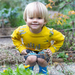 Blonde boy crouching in a garden bed wearing yellow Oomph and Floss meerkat jumper