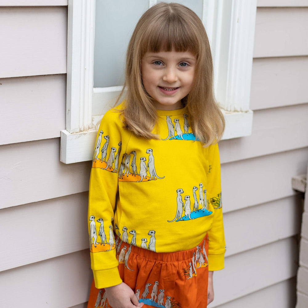 Girl wearing kids meerkat jumper in bright yellow and matching orange girls meerkat skirt