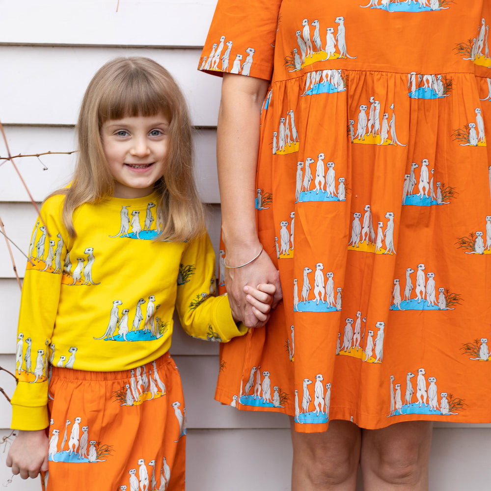 Mummy and daughter in matching outfits. Both feature the same hand drawn illustrations of meerkats.  The Mums dress is in a vibrant flame orange and matches the girls skirt out of the same fabric.  The girls wears a contrasting yellow jumper in the same meerkat print.