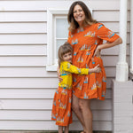Mummy and Me matching meerkat outfits.  Bright scandi-style clothing by Australian owned brand Oomph and Floss. Australian stockists of scandi like brand.  Matching orange meerkat adult dress and girls skirt.  Matching yellow meerkat jumper.