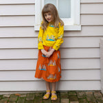 Girl wearing matching meerkat print clothing.  Yellow meerkat jumper and matching orange meerkat skirt