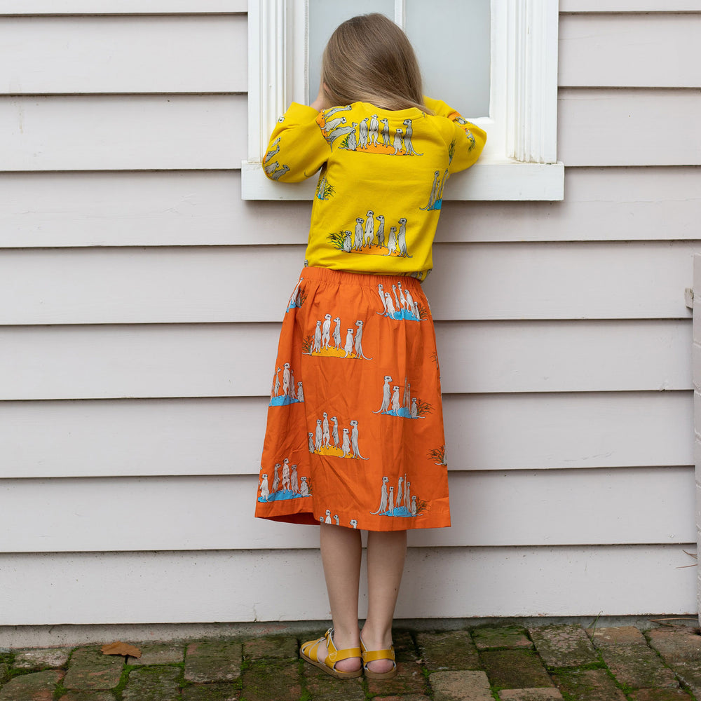Back view of girl wearing orange meerkat skirt by Oomph and Floss and matching yellow meerkat jumper