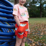Girl wearing shorts with Puckle Duck design in vibrant cherry tomato red.  She has her hand in her pocket.  She is wearing a matching tshirt out of the same fabric pattern in a contrasting pearly peach colour.  Both designs feature the Puckle Duck family.