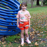 Girl wearing peach coloured duck tshirt and matching kids drawstring duck shorts with pockets