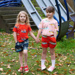 Two girls holding hands, each wears matching unisex colourful clothes in matching prints.  Girl on left wears red tee with meerkat print and matching meerkat shorts in dark grey.  Girl on right wears duck family tee in a peach colour with matching duck family shorts in a red colour.