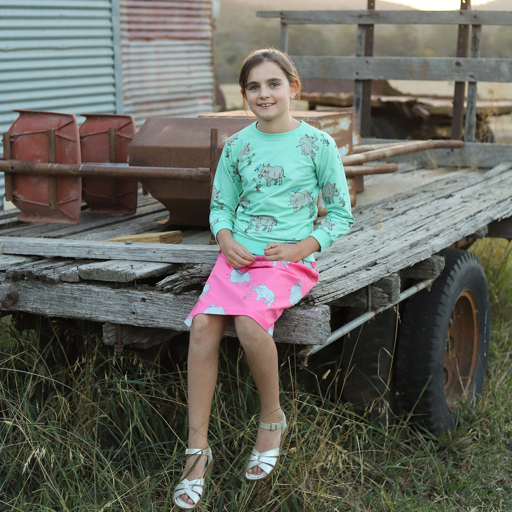 Girl wearing lightweight jumper in biscay bay blue with repeat pattern of hand-drawn illustration of rhinoceros.  The girl is sitting on the back of an old dilapidated farming trailer and is wearing a vibrant pink knee length skirt featuring a matching rhino print to her jumper.