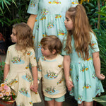 Family wearing matching duck print outfits. The girls wear duck dresses in cream and cool mint blue.  The boy wears a duck jumper in cream and matching mint shorts.  The Mum wears a gathered waist womens dress in matching duck print.