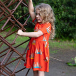 Young girl wearing girls meerkat dress with pockets.  Oomph and Floss dress with meerkats