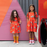 Two girls wearing matching red dresses with pockets and meerkat print