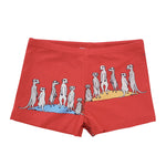 Flatlay picture of boys swimshorts in a cherry tomato red featuring a hand drawn illustration of a family of meerkats in a repeat pattern