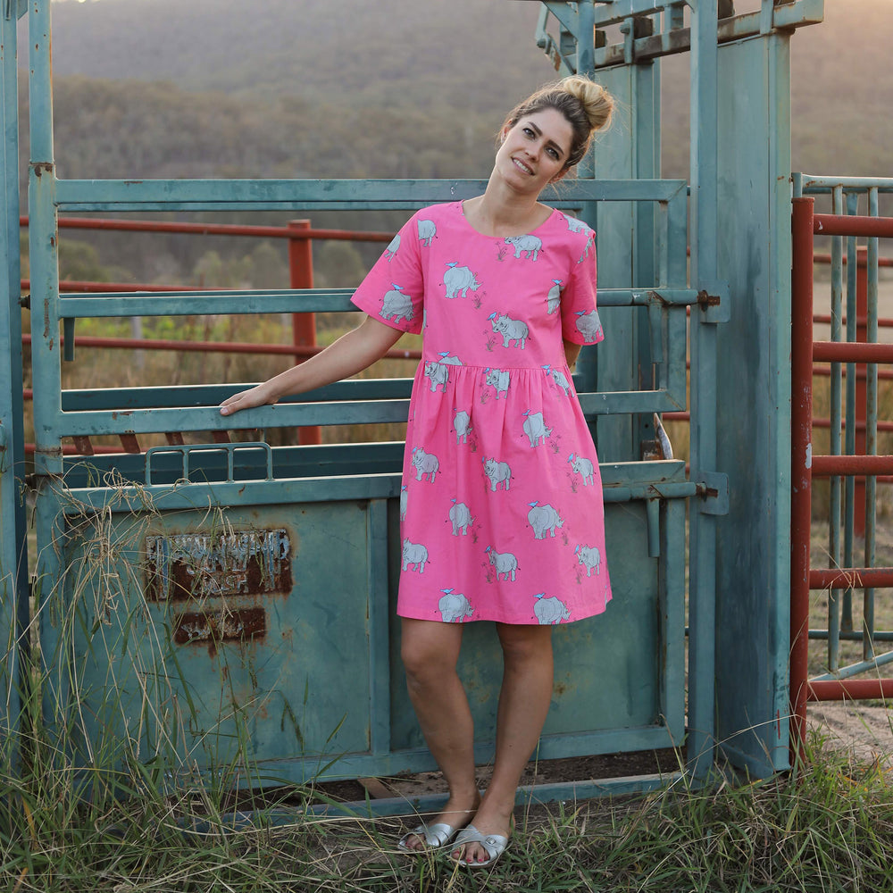 "Woman wearing vibrant pink dress with a gathered drop waist and a knee-length skirt.  The dress features hand-drawn illustrations of ""Popcorn"" the Rhino."