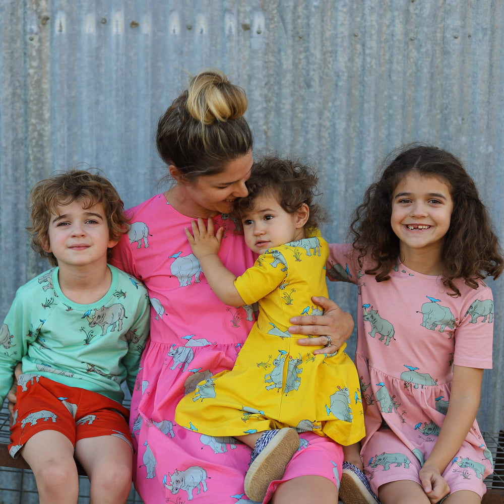 Woman with 3 children, all are wearing clothing from the same fabric featuring the same grey rhinoceros print in a repeat pattern, each is in a different colour biscay bay jumper, tigerlily red shorts, pink lemonade adult dress, lemonzest twirling dress, dusty pink aline dress.