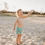Blonde toddler at the beach wearing biscay bay coloured swim shorts featuring a rhino print in a repeat pattern