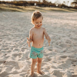 Happy boy at the beach playing in sand wearing Oomph and Floss swimmer shorts with Popcorn the Rhino print